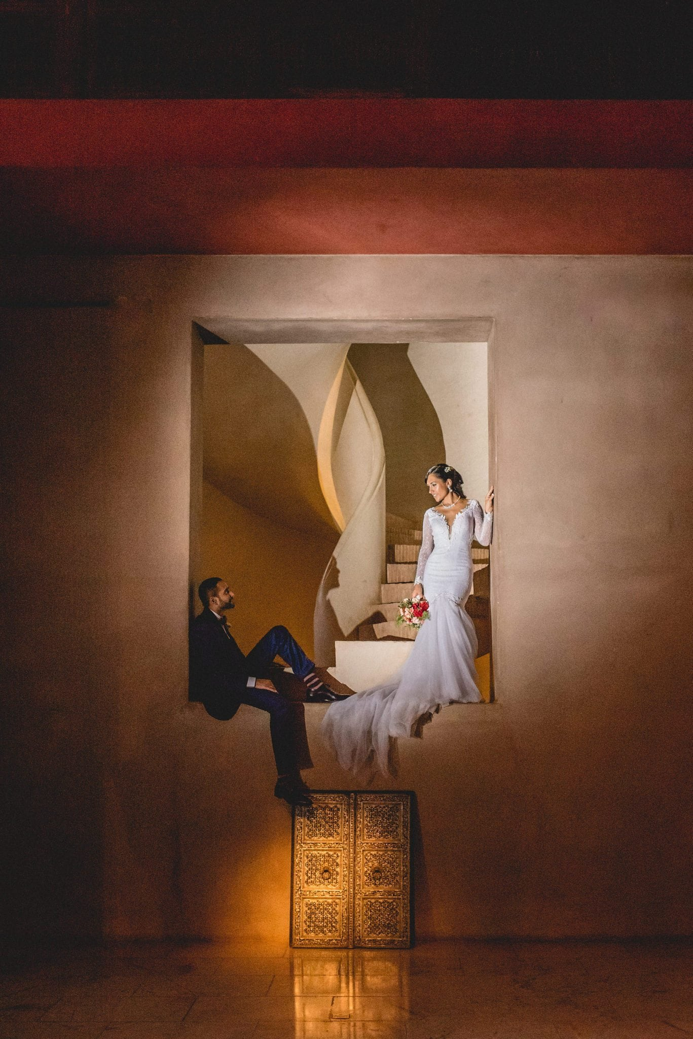 The bride and groom stand dramatically in one of the alcoves near the base of the Ksar Char Bagh staircase.
