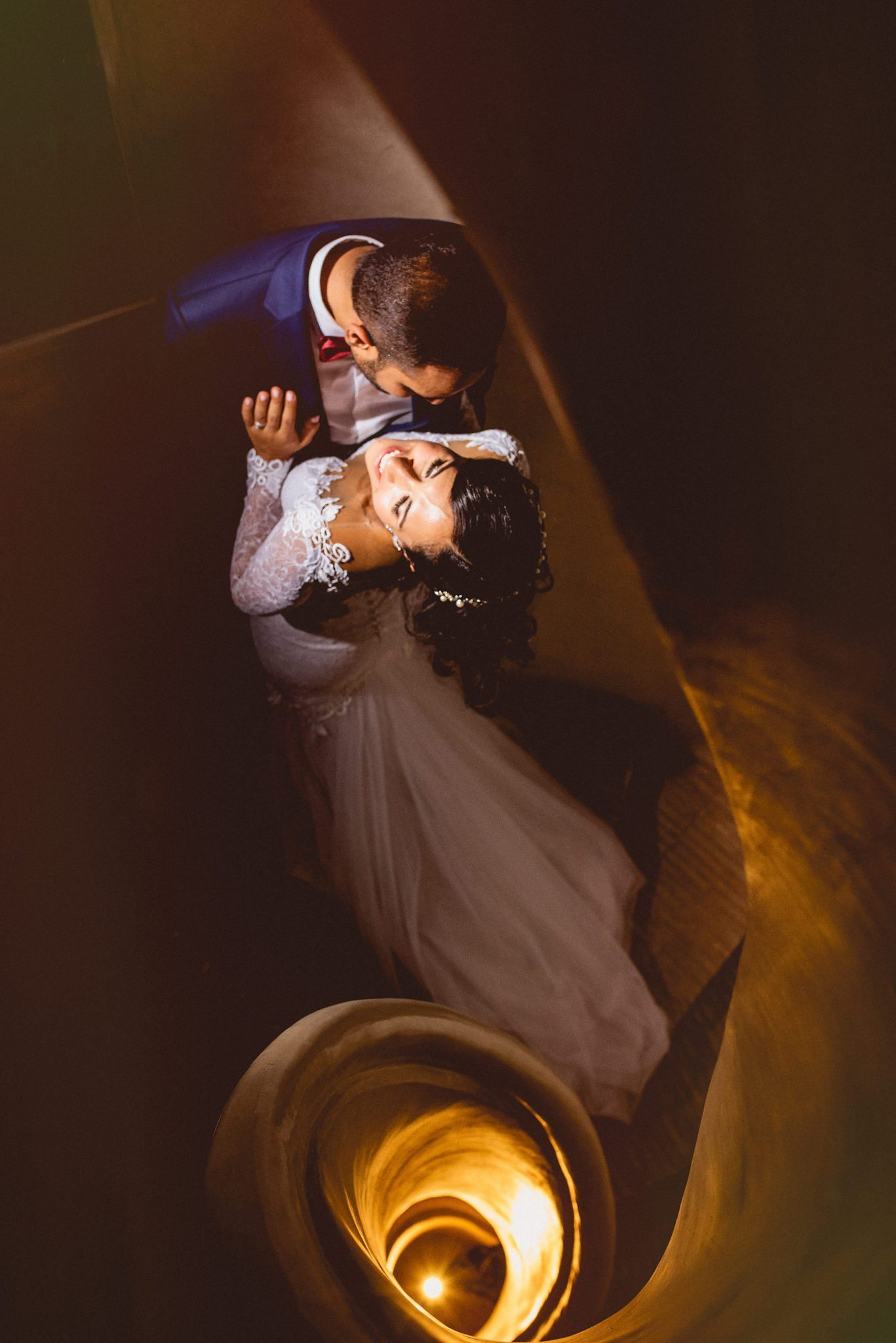 The glamorous couple hold each other close on the spiral staircase and are photographed from above looking down