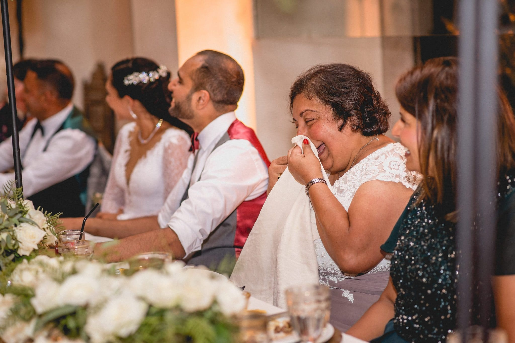 The groom's mother wipes her eyes on a napkin after a fit of the giggles during the speeches