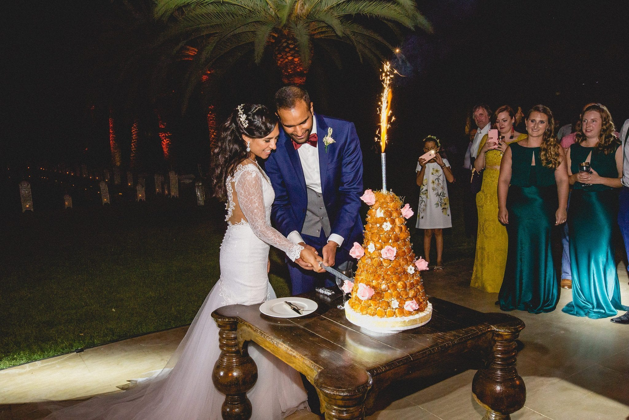 The couple cut their croque en bouche cake outside