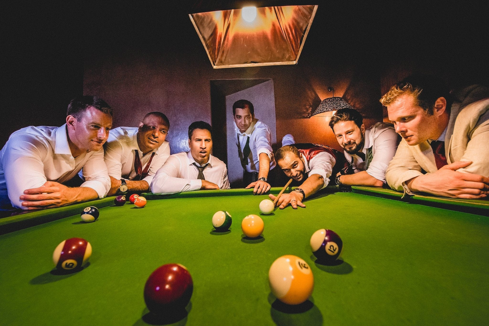 The groomsmen and ushers pose around the pool table as the groom prepares to take a shot