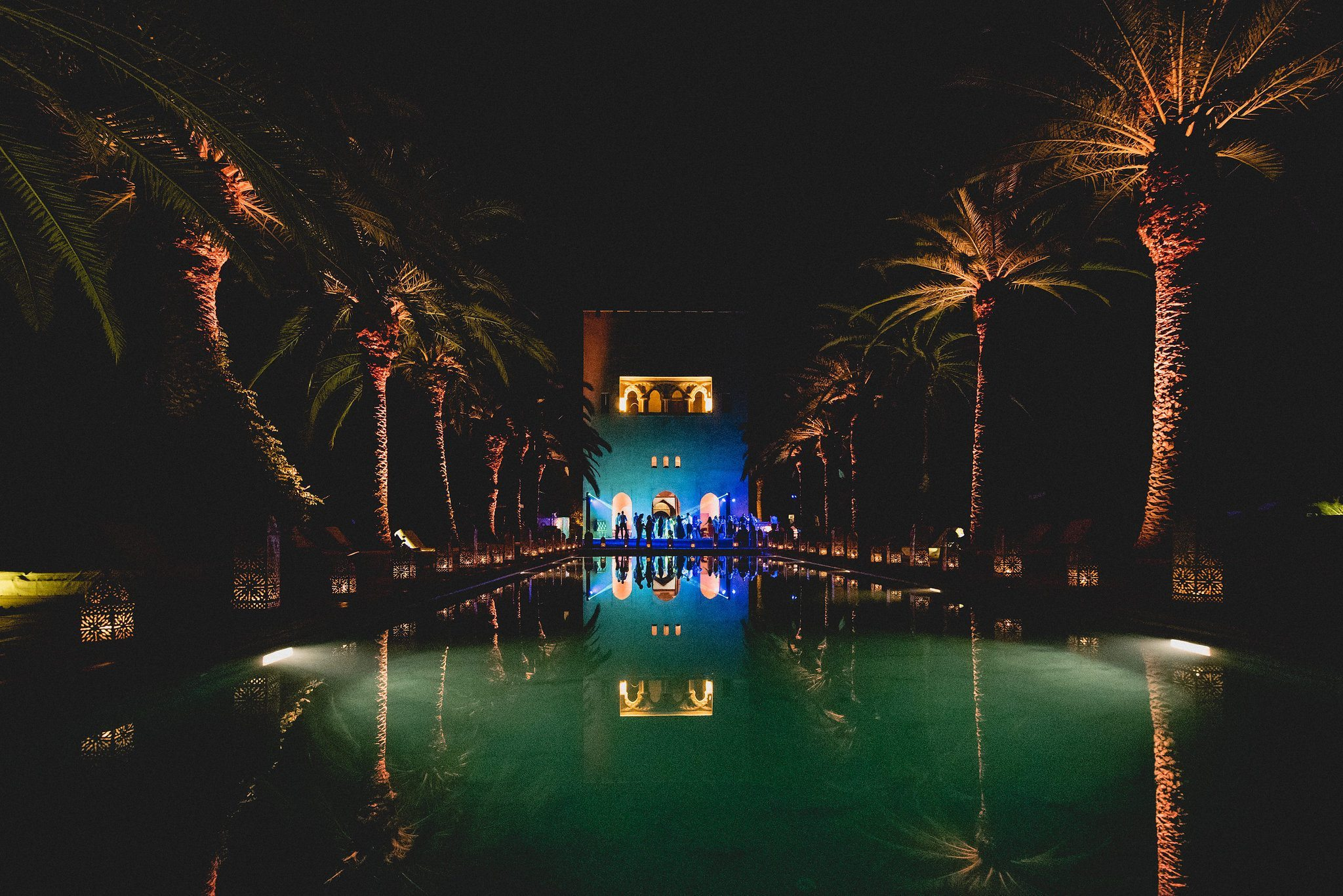 The venue is lit up by party lights and the pool glows as the dancing continues