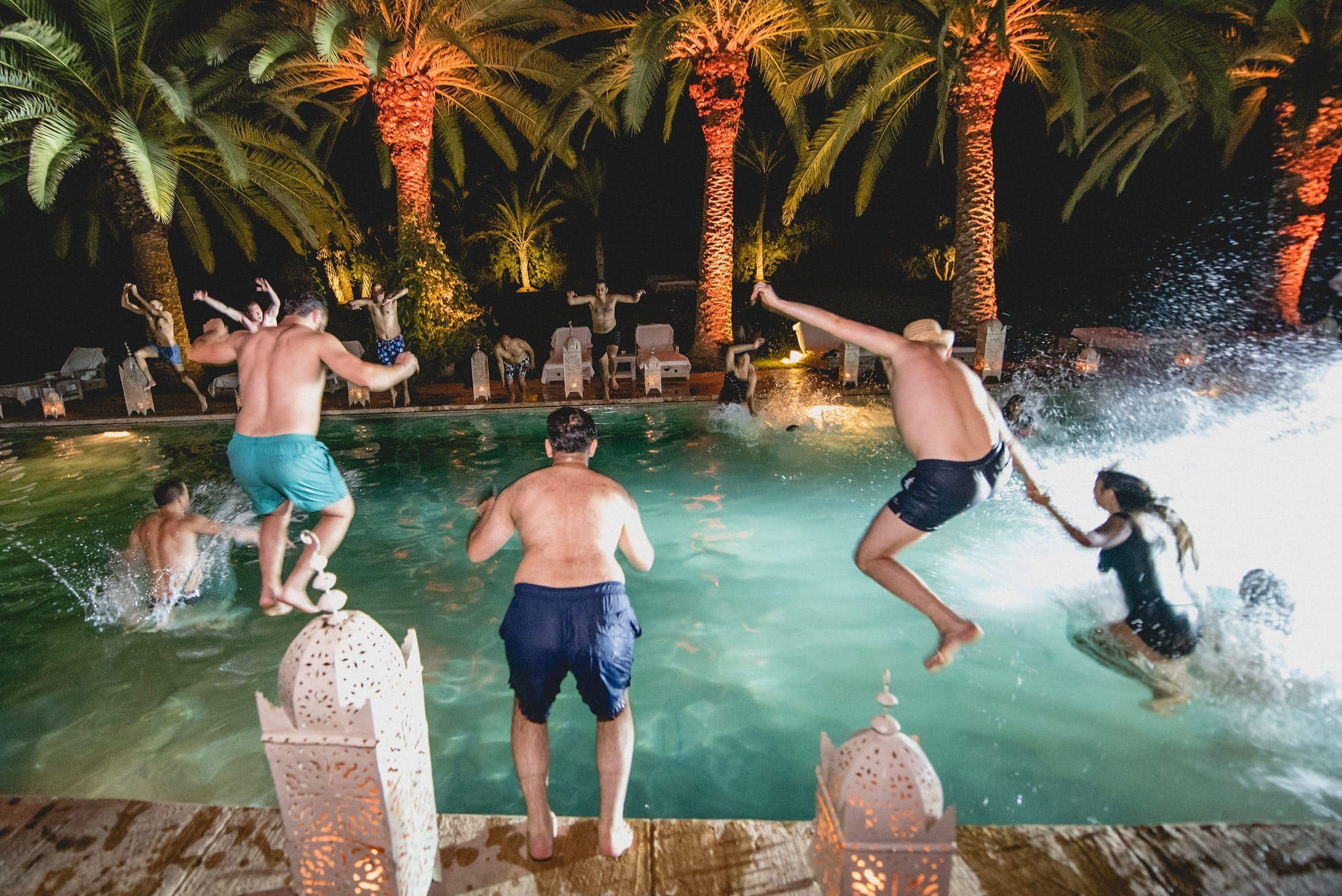 A group of guests jump into the pool