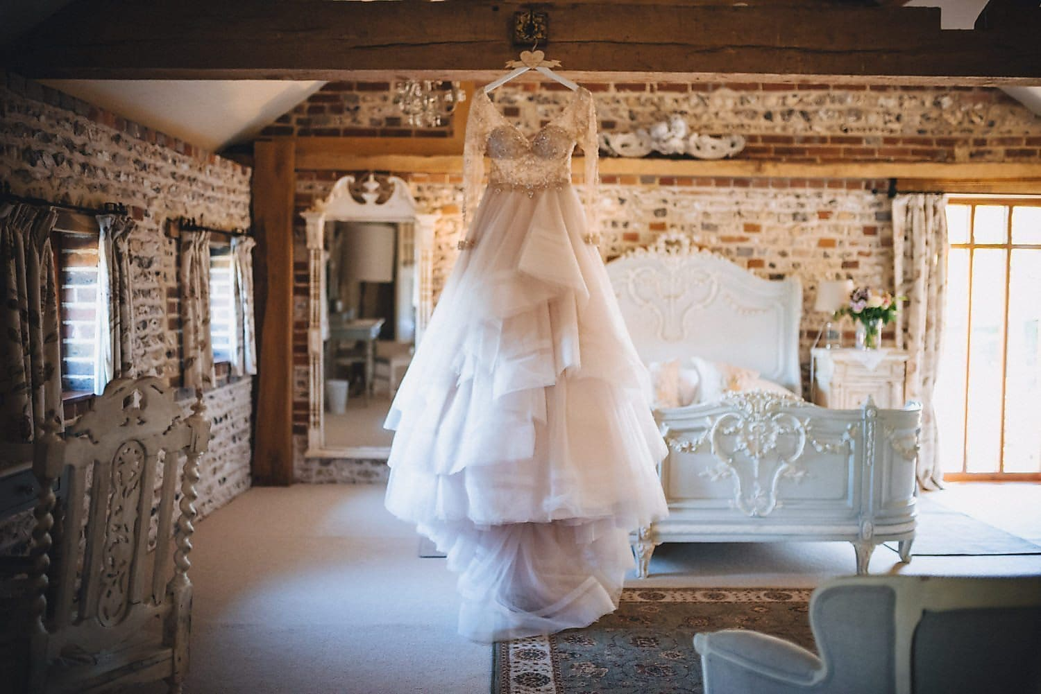 The bride's Martina Liana gown hangs from a beam in the ceiling of the room where she's getting ready.