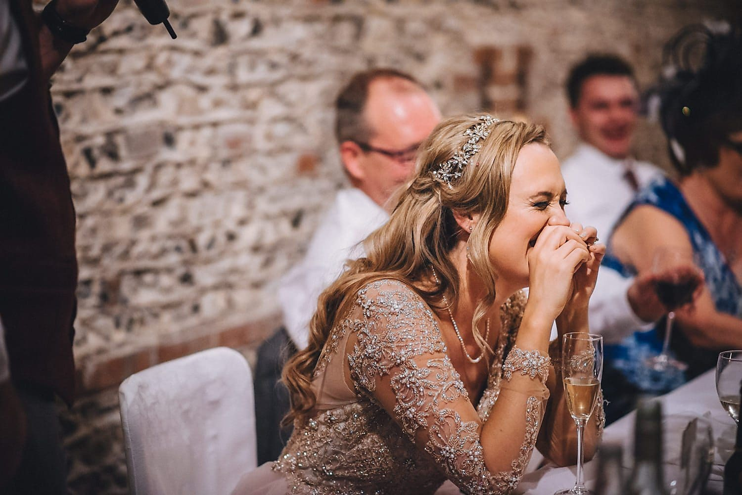 Bride bursts out laughing and covers her face during the speeches