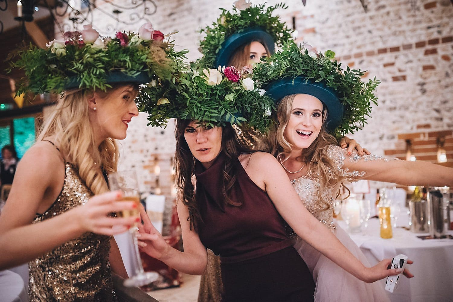 The bride and three female guests pose jokily with bowler hats decorated in loads of flowers