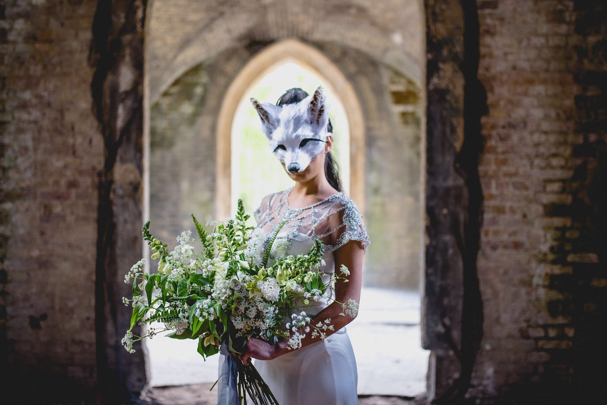 Close up of bride in fox mask and her large, loose bouquet tied with silk ribbon