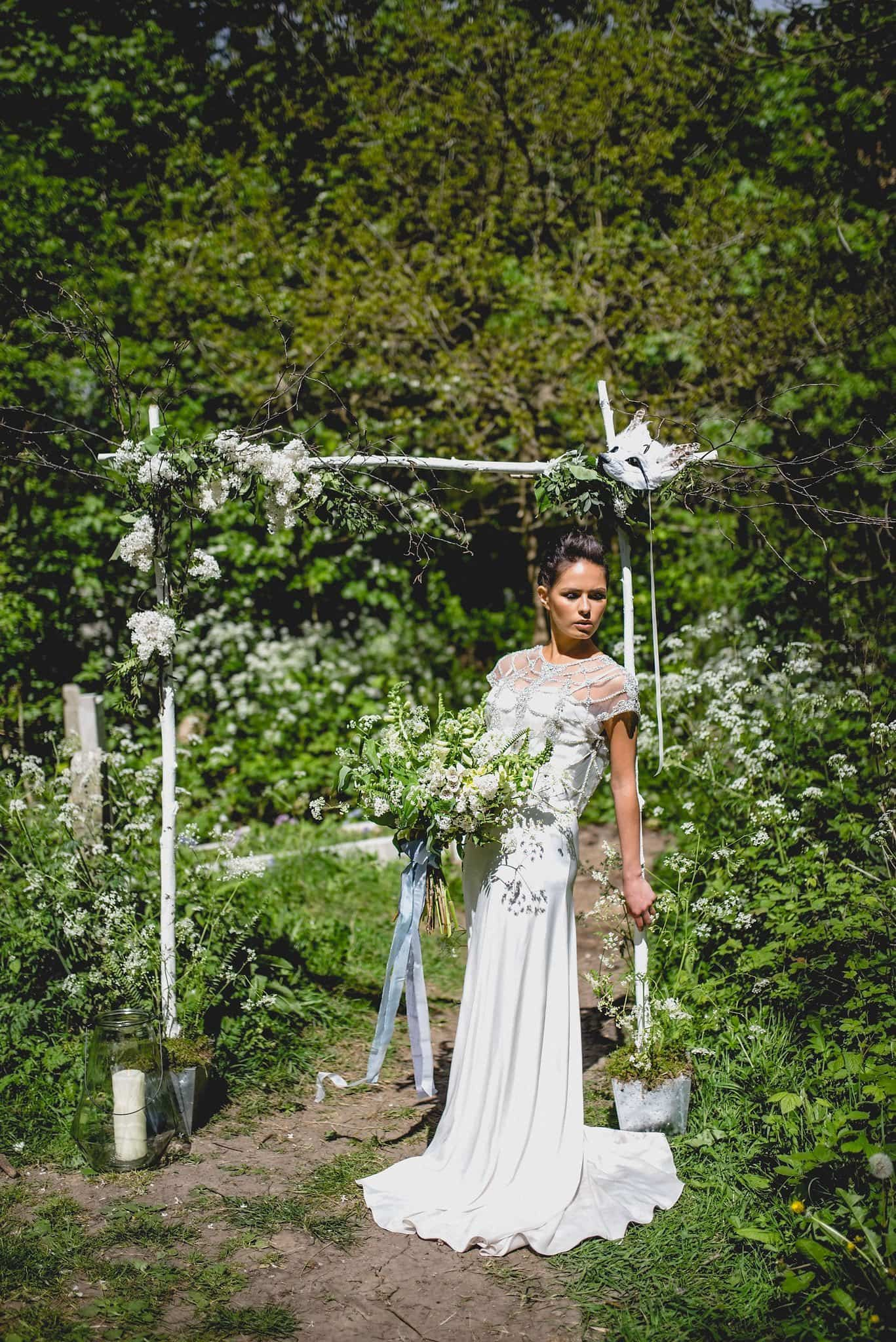 Bride leans against wooden arch decorated with flowers, with feather fox mask in top right corner