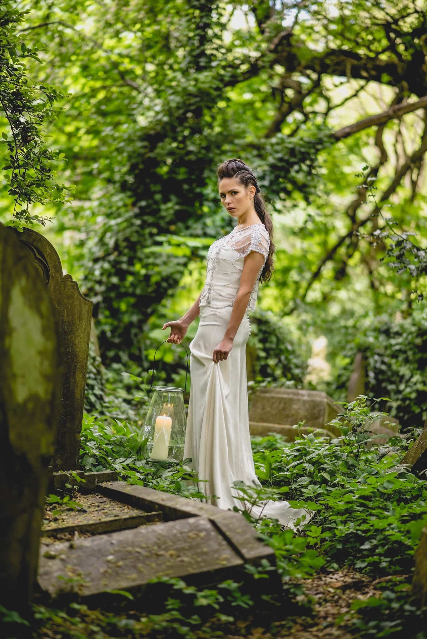 Bride stands among the graves in Abney Park, holding a lantern