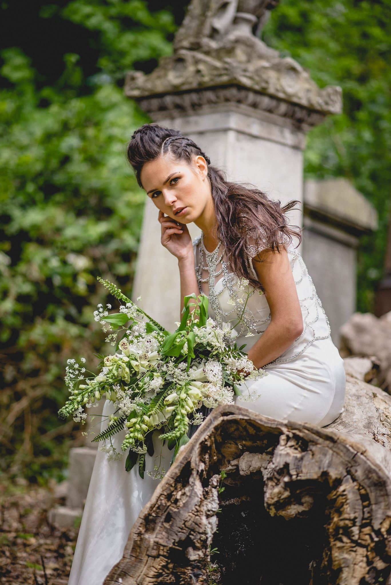 Bride sits on fallen tree, leaning forward and resting her chin on her hand