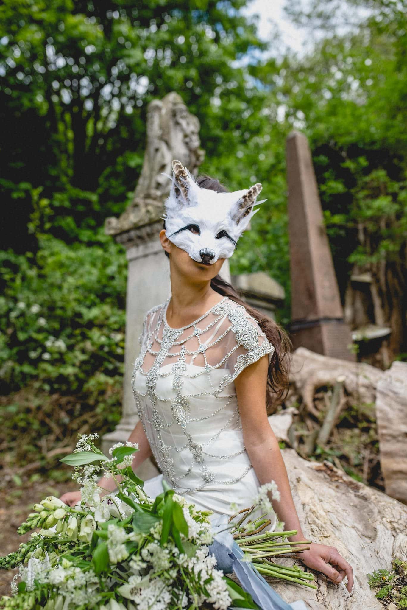 Bride seated on fallen tree wearing feather fox mask among the tombs in Abney Park Cemetery