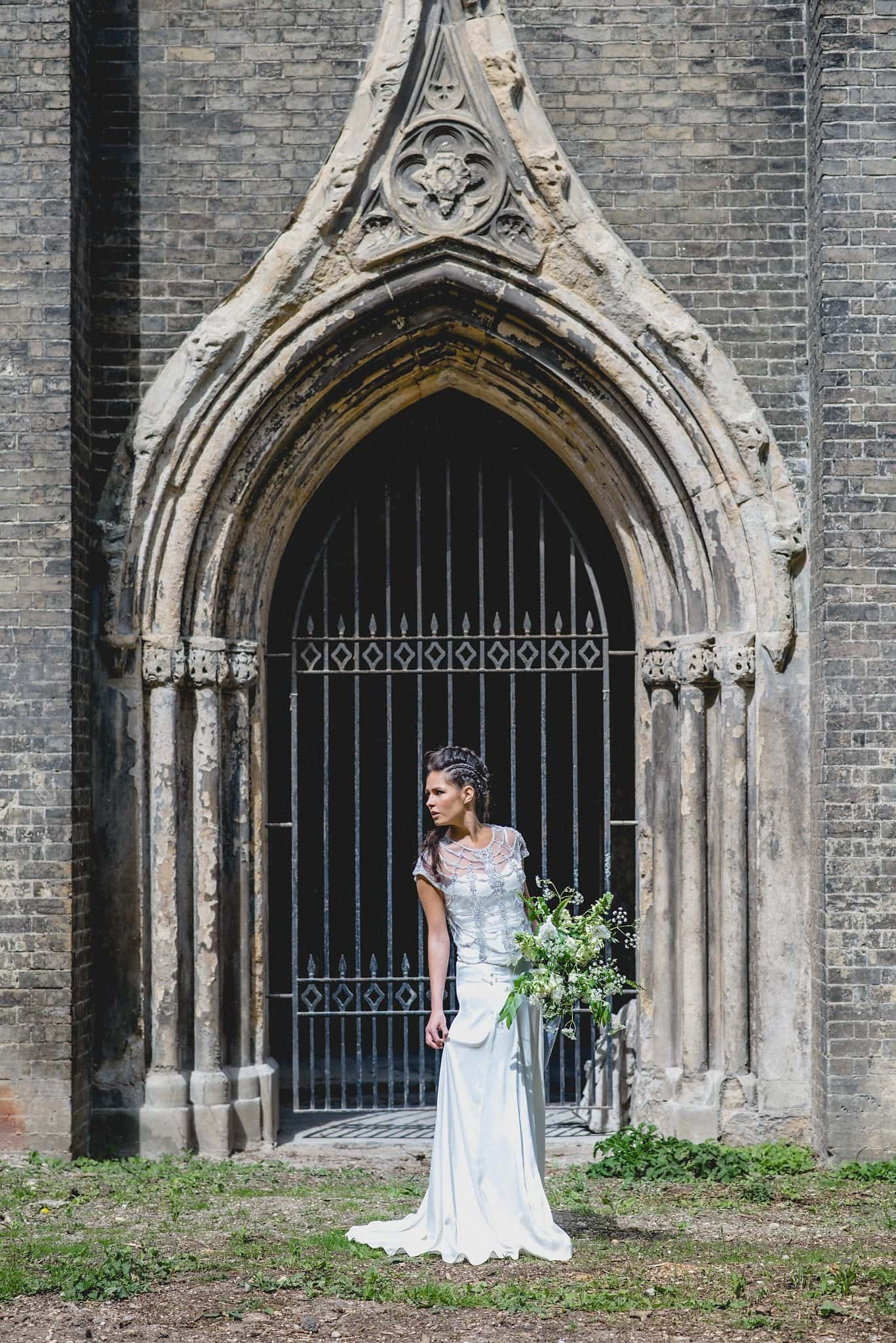 Bridal portrait in front of the entrance arch holding large bouquet of wild flowers