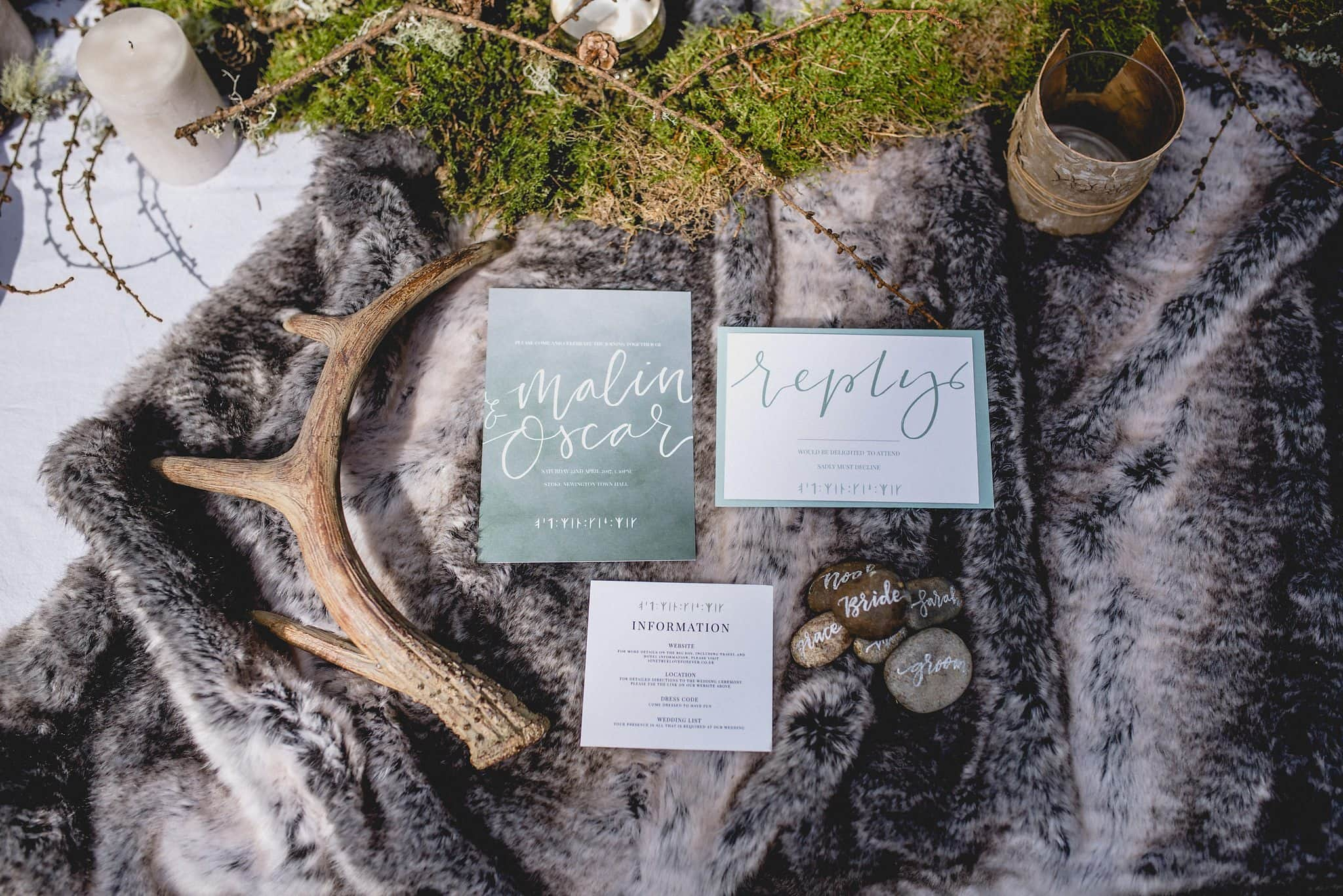 Flatlay of sage green stationery on grey fur throw with antler, moss and pebbles