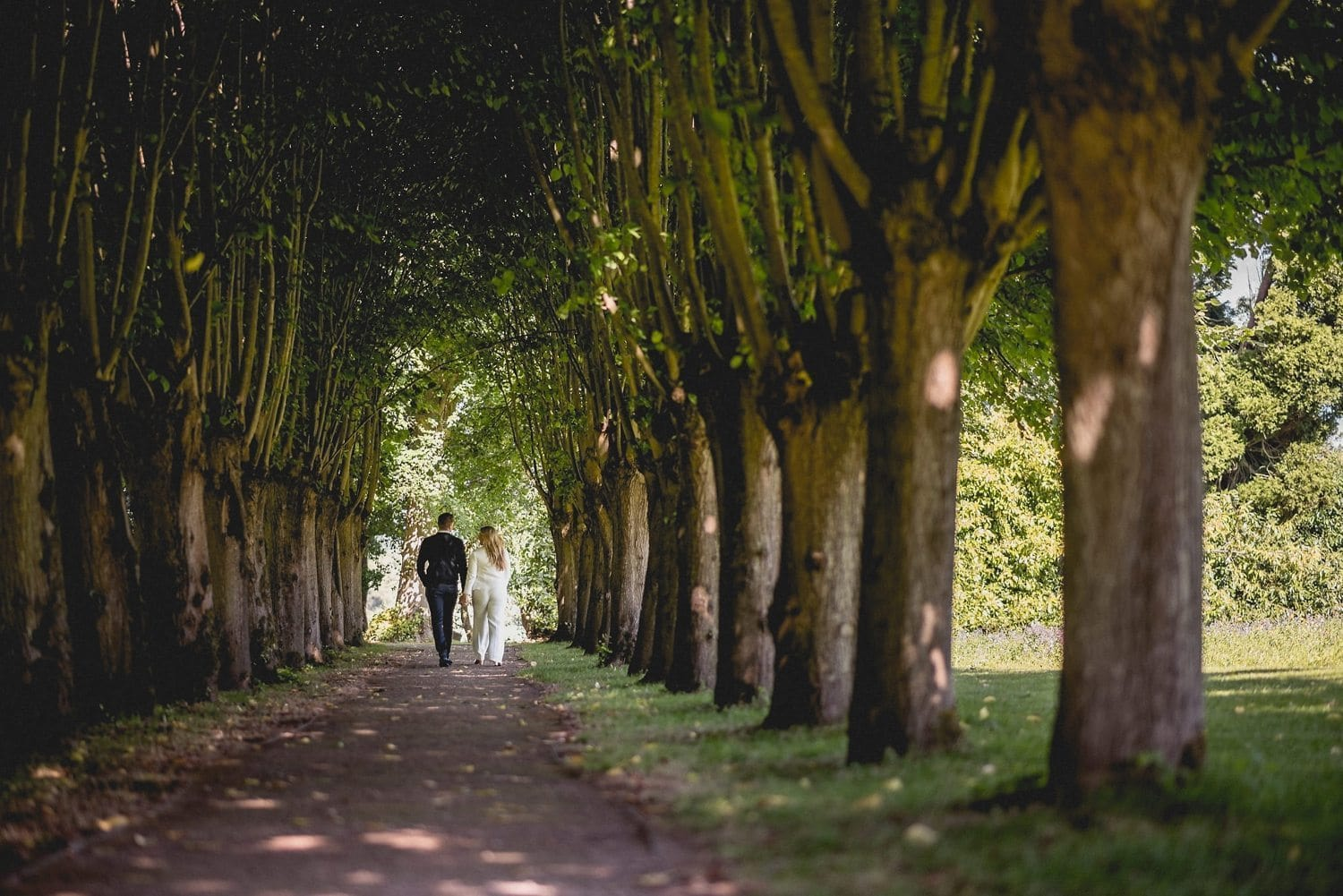 Couple walking under the tree tunnel at Coworth Park