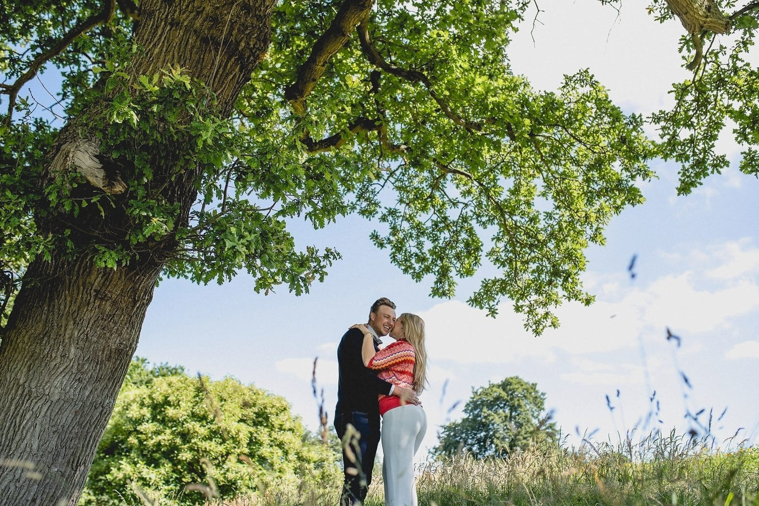 Couple hugging under the big oak tree at Coworth Park