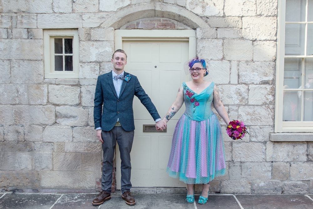 Bride and groom hold hands. Bride wears bespoke pink and turquoise dress from The Couture Company