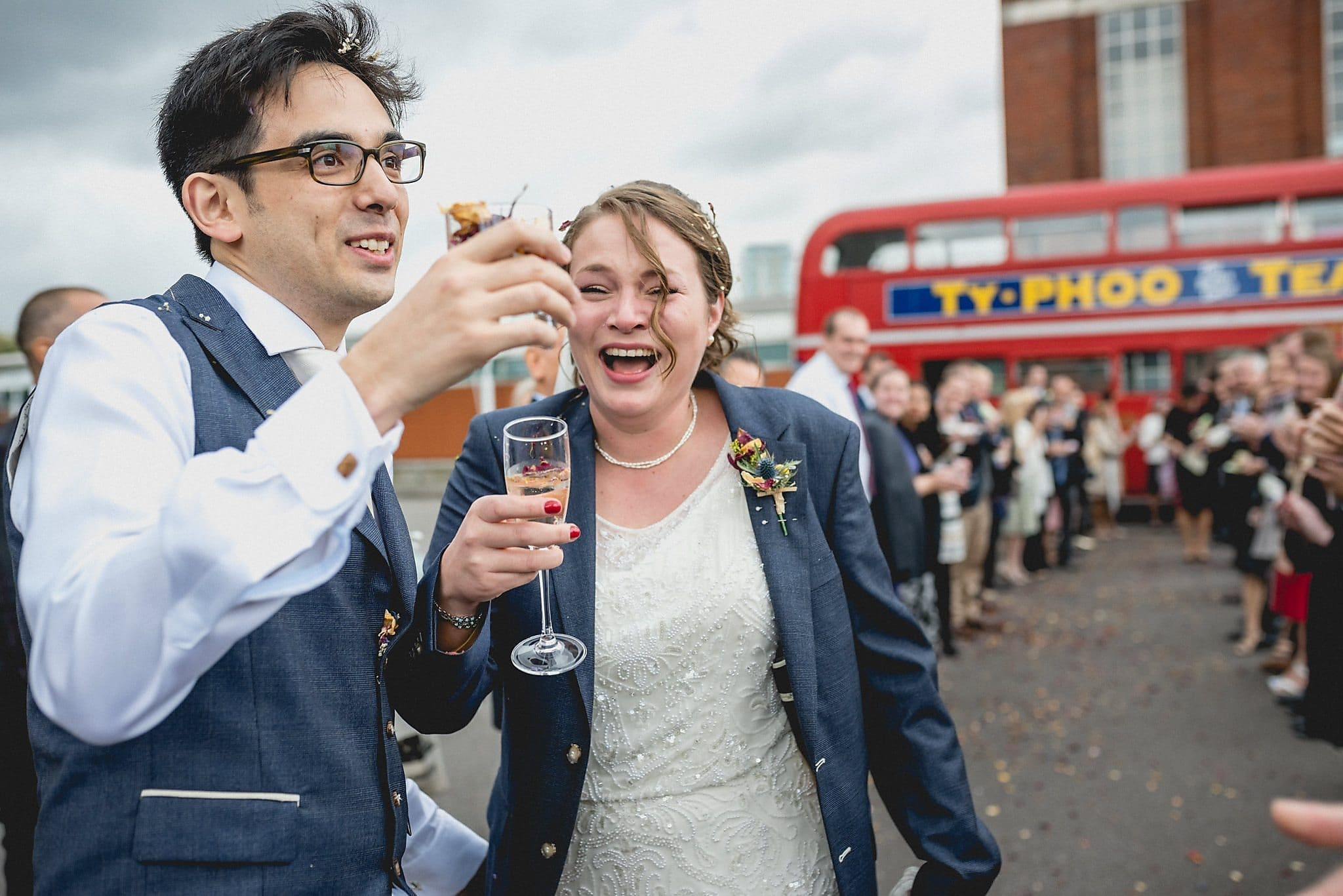 Bride and groom laughing at their confetti filled glasses at the west reservoir centre