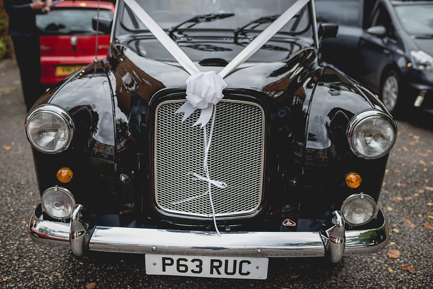 Black cab wedding car decorated with white ribbon