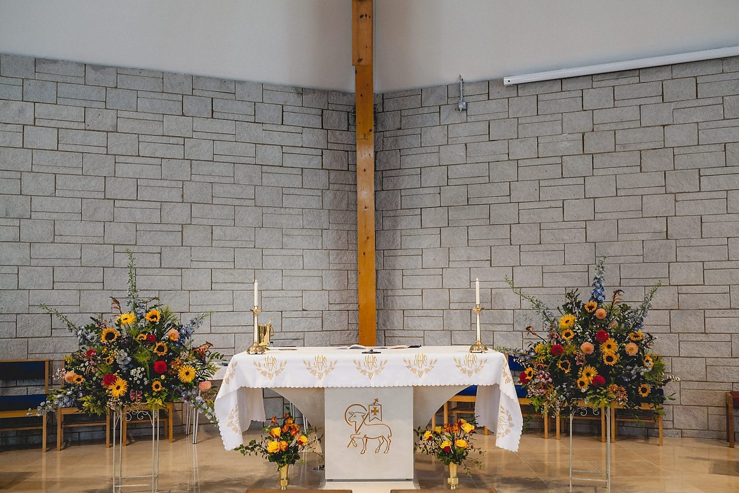 The altar at the church is flanked by large floral arrangements with red, yellow and blue flowers