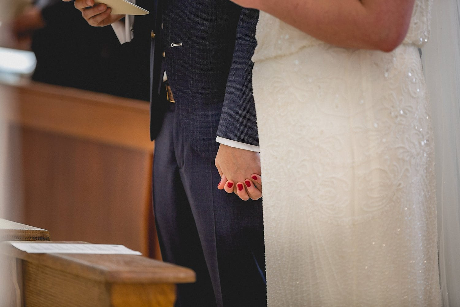 The bride and groom hold hands at the altar
