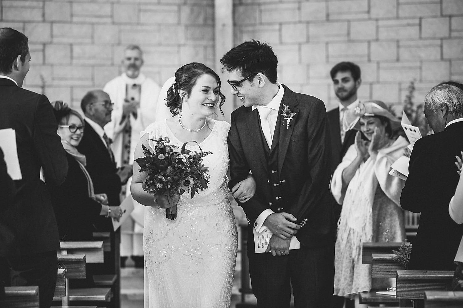 A black and white shot of the couple walking down the aisle together, smiling and gazing at each other