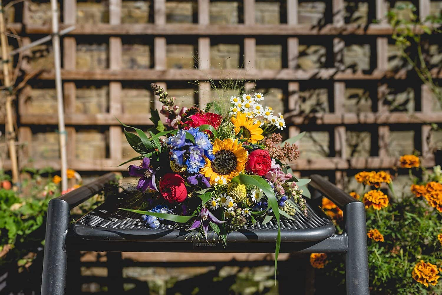 Close up of colourful bridal bouquet featuring daisies, roses and sunflowers