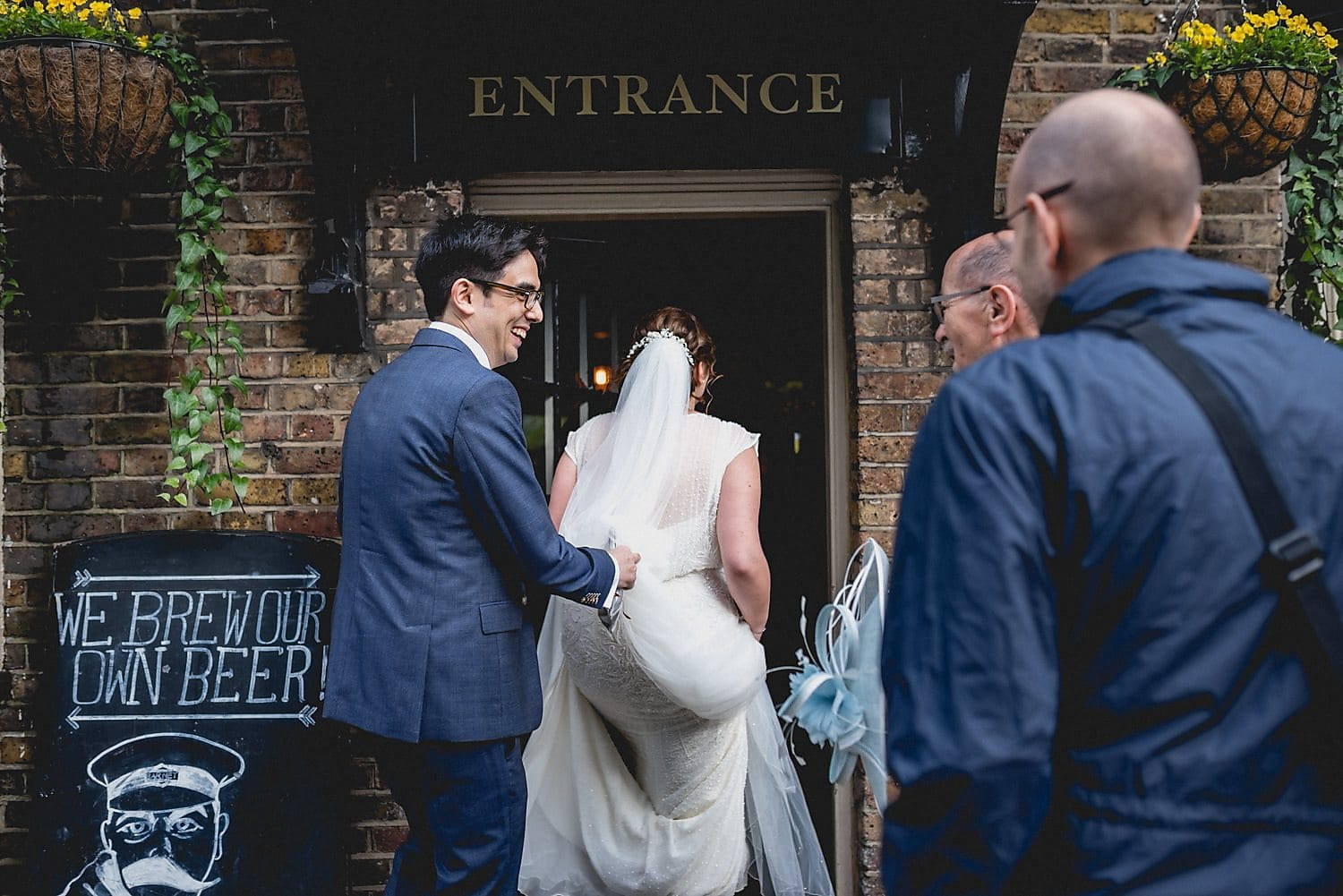 Groom holds up his bride's dress as she enters the pub