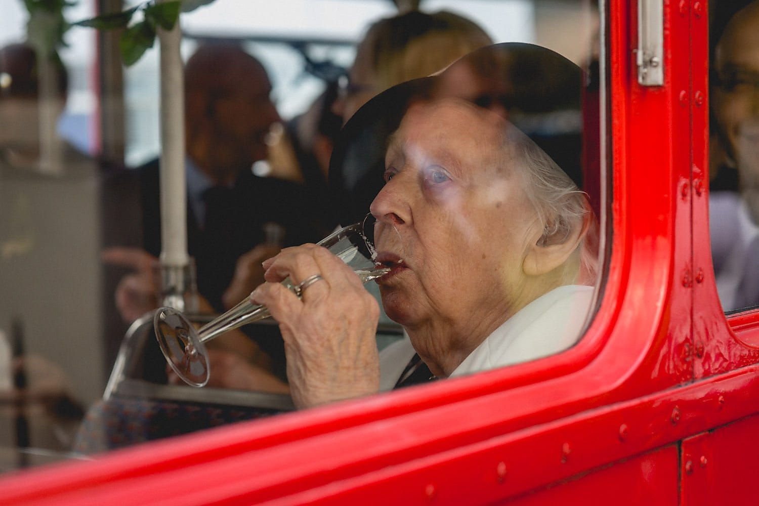 Bride's grandmother sips champagne on the bus on the way to the West Reservoir Wedding reception