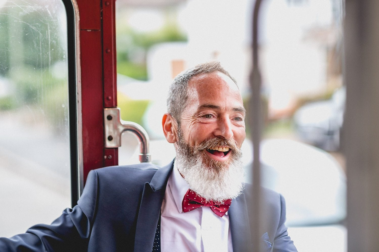 A male guest with red spotty bow tie laughs on board the wedding bus