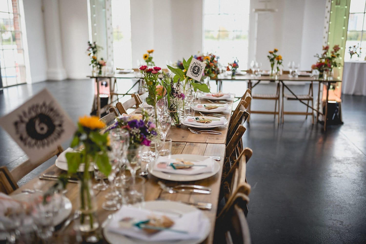 Close up of tablescape with bright flowers in bud vases