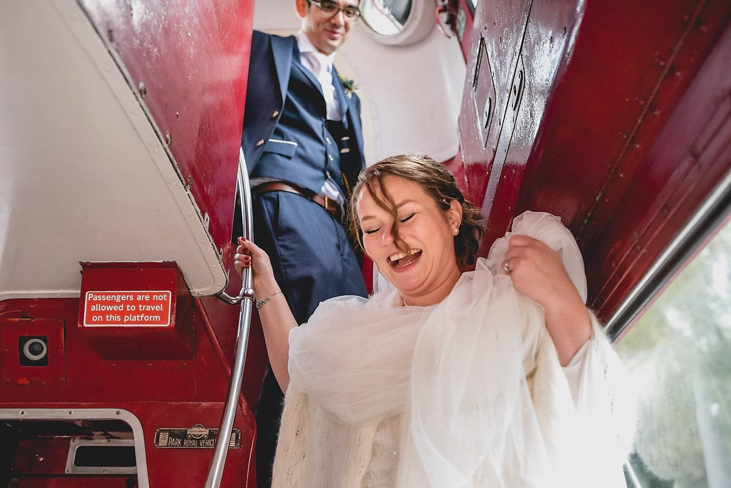 The bride laughs and holds up her dress as she makes it down the narrow stairs of the bus