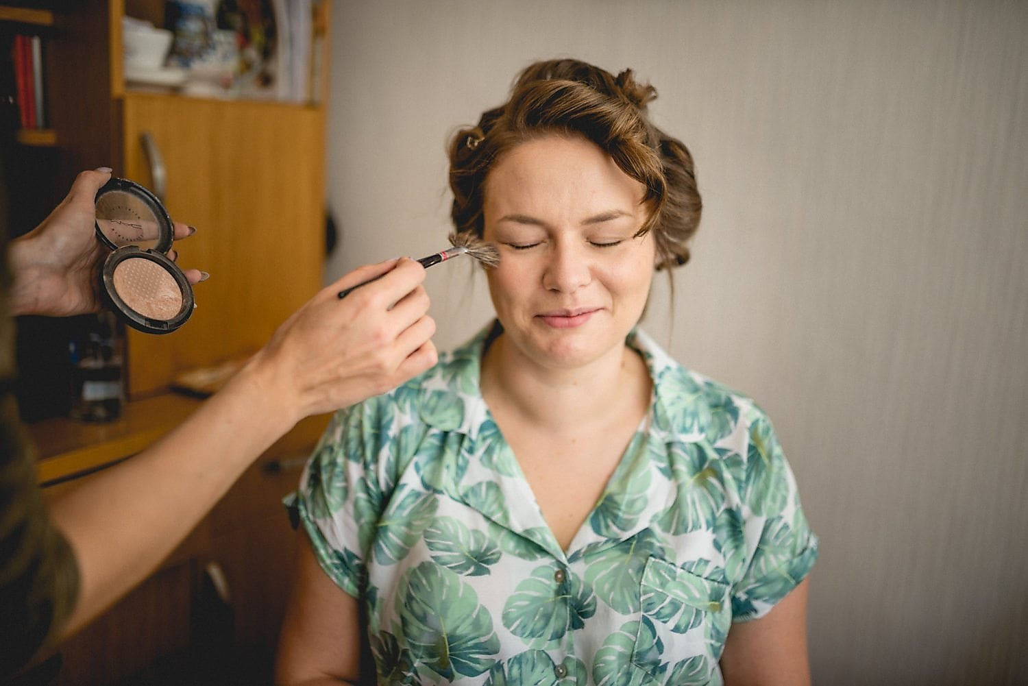 Bride gets her makeup done on her wedding day