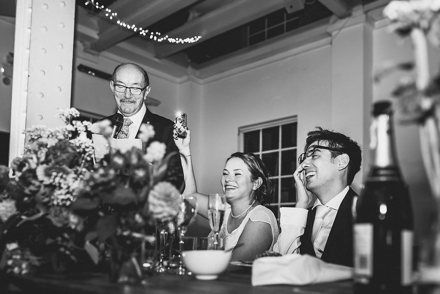 The father of the bride makes his speech, as the bride waves a lighter in the air, laughing