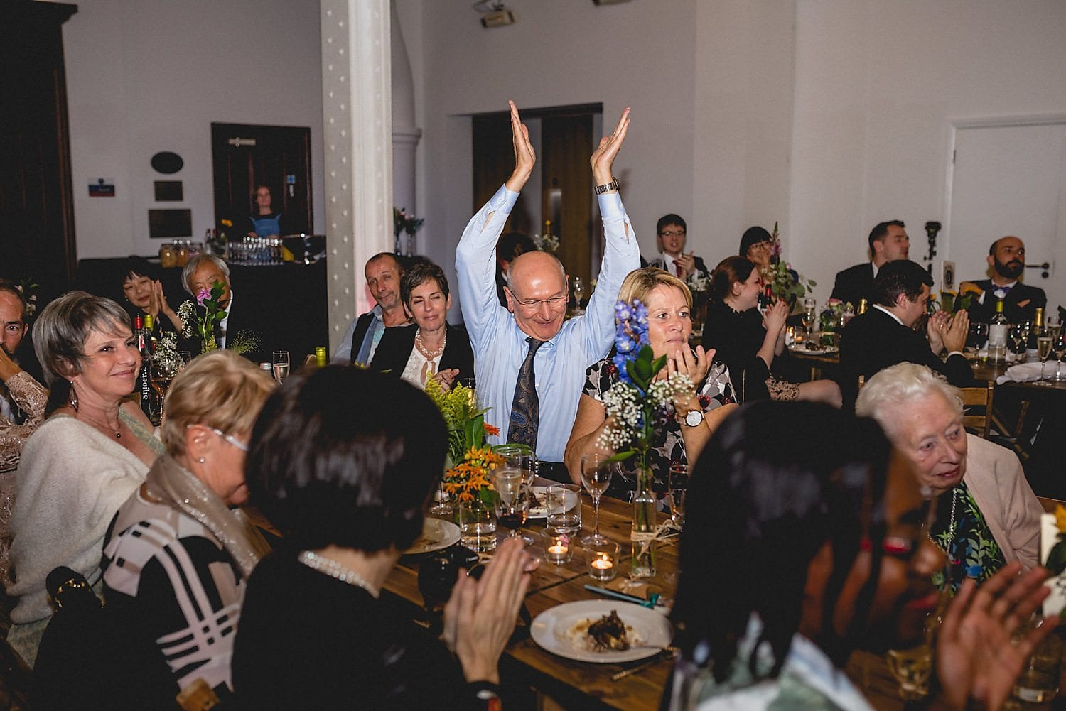 A guest applauds with his hands in the air during the speeches