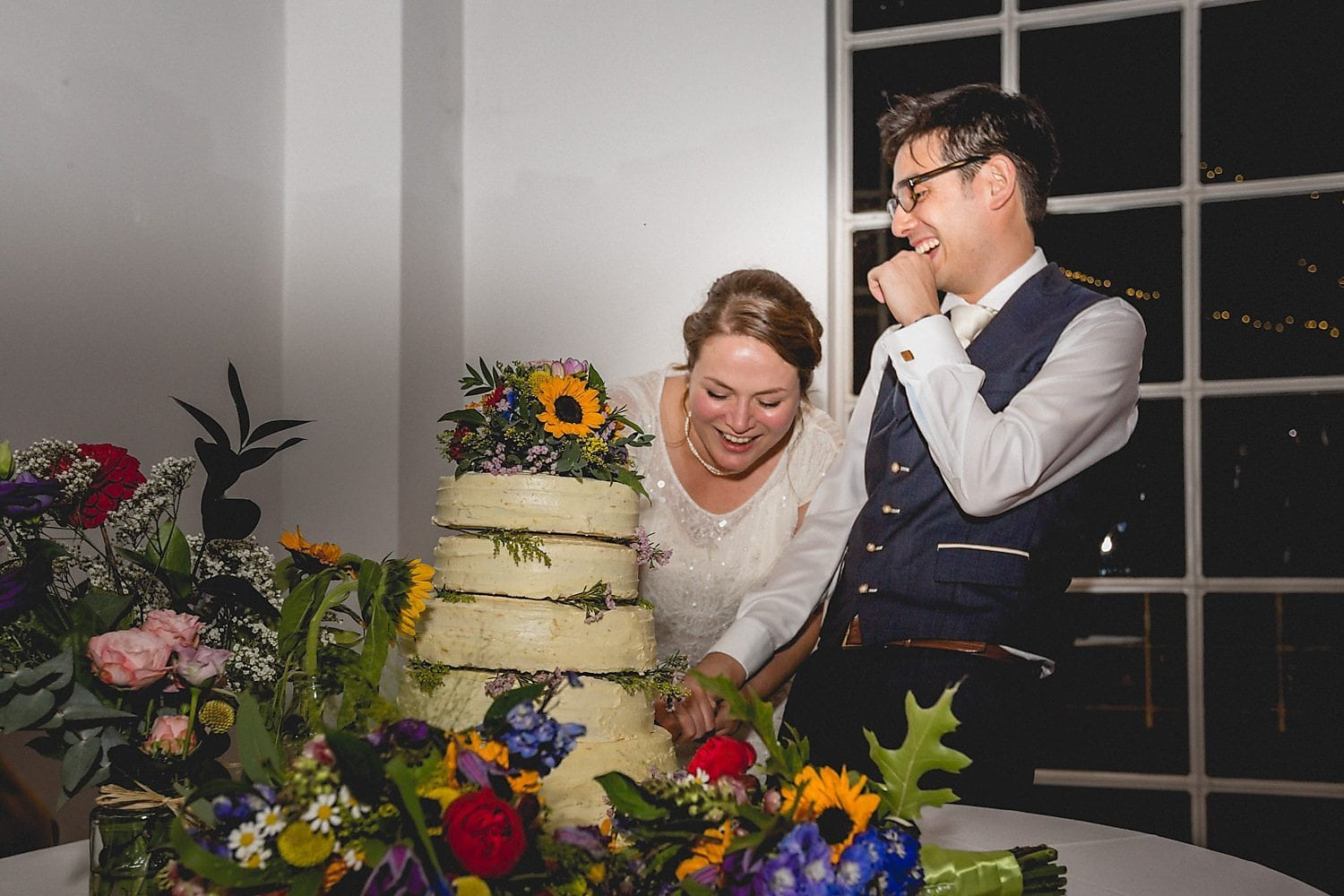 The bride and groom laugh as they cut their wedding cake