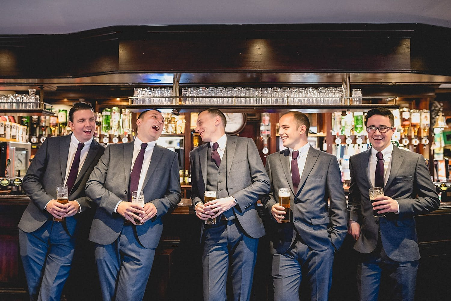 Groom and groomsmen laugh together with a pint on the morning of the wedding
