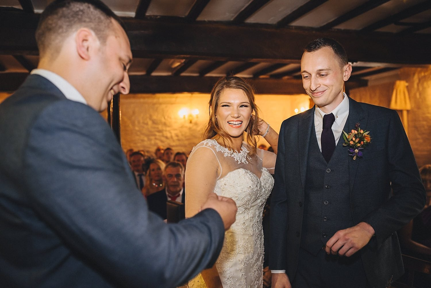 Bride and groom laugh during their ceremony at Coltsford Mill