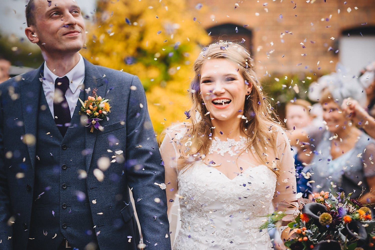 Bride and groom walking through a confetti shower at Coltsford Mill