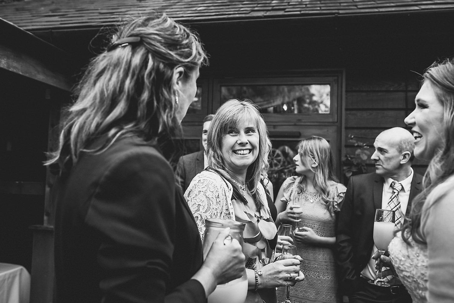 Wedding guests chatting with the bride at Coltsford Mill