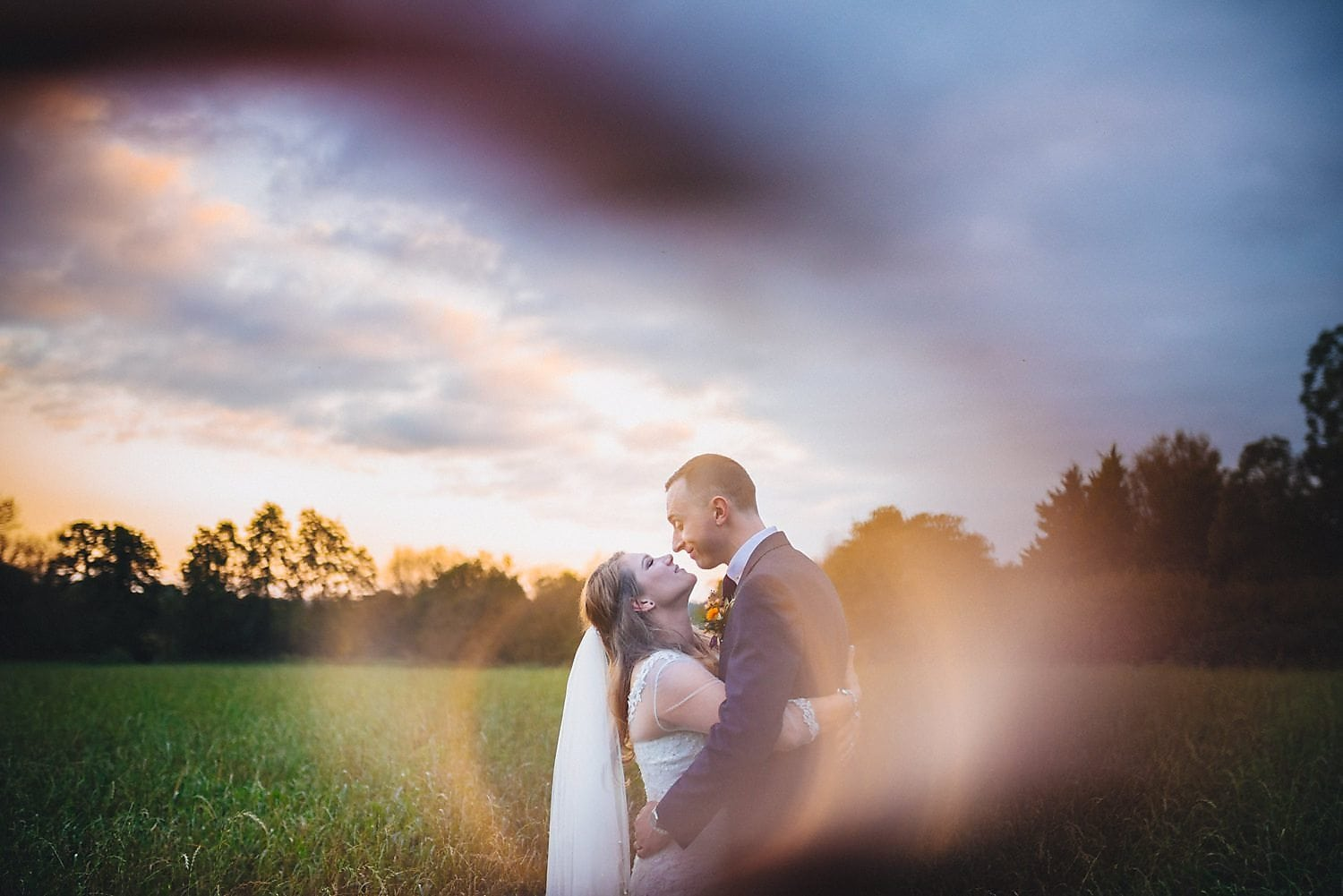 Bride and groom embrace in a field at sunset