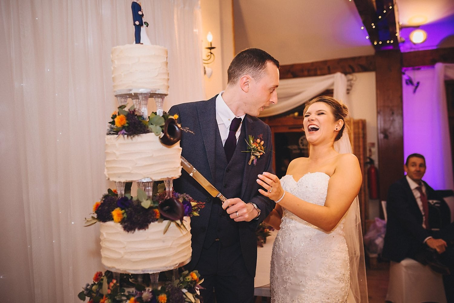 Bride and groom laughing as they cut their wedding cake