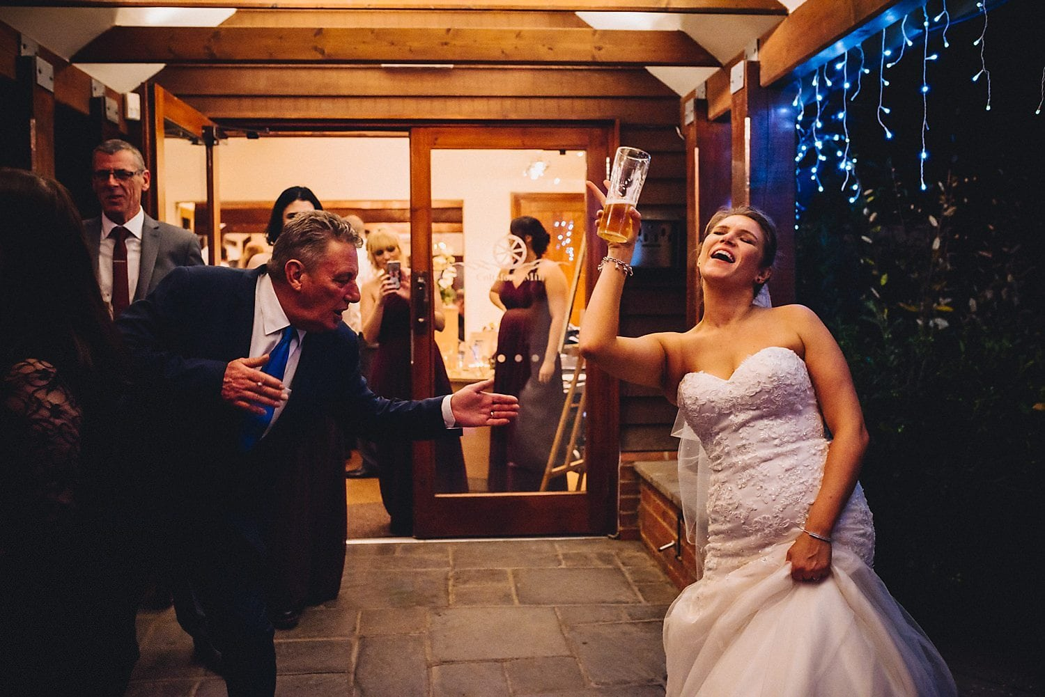 Bride dancing and singing with her uncle at her wedding while holding a pint