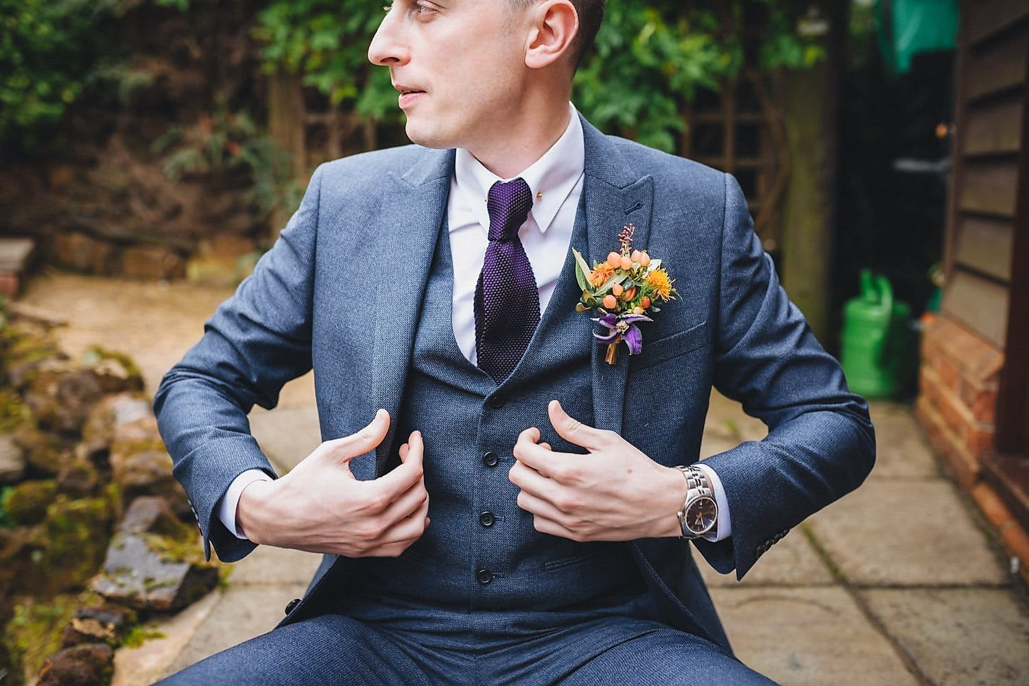 Portrait of groom in grey suit and waistcoat and large purple and orange floral buttonhole. He straightens his jacket and looks off to one side.