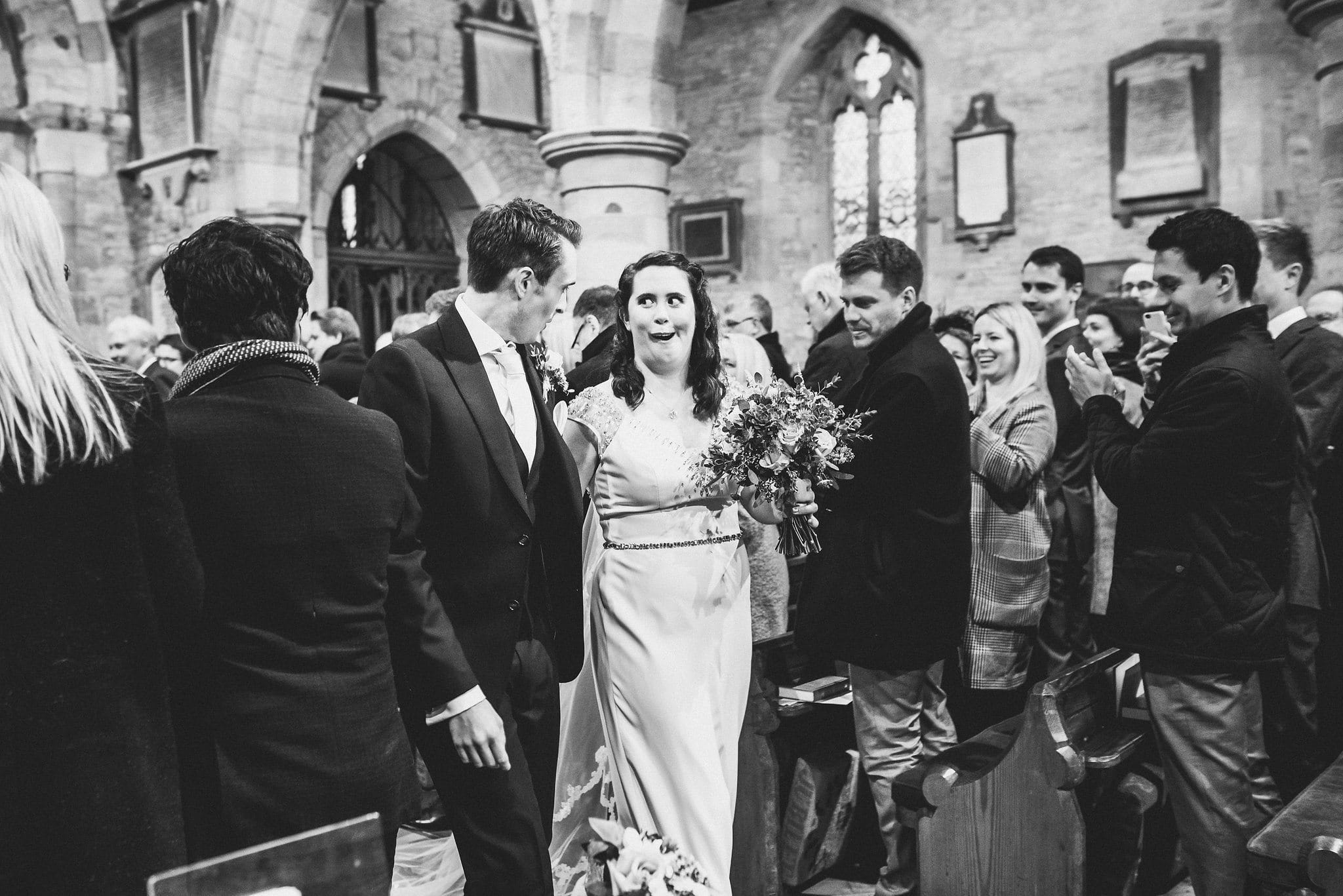 Black and white shot of bride and groom walking back down aisle. Bride pulling funny face