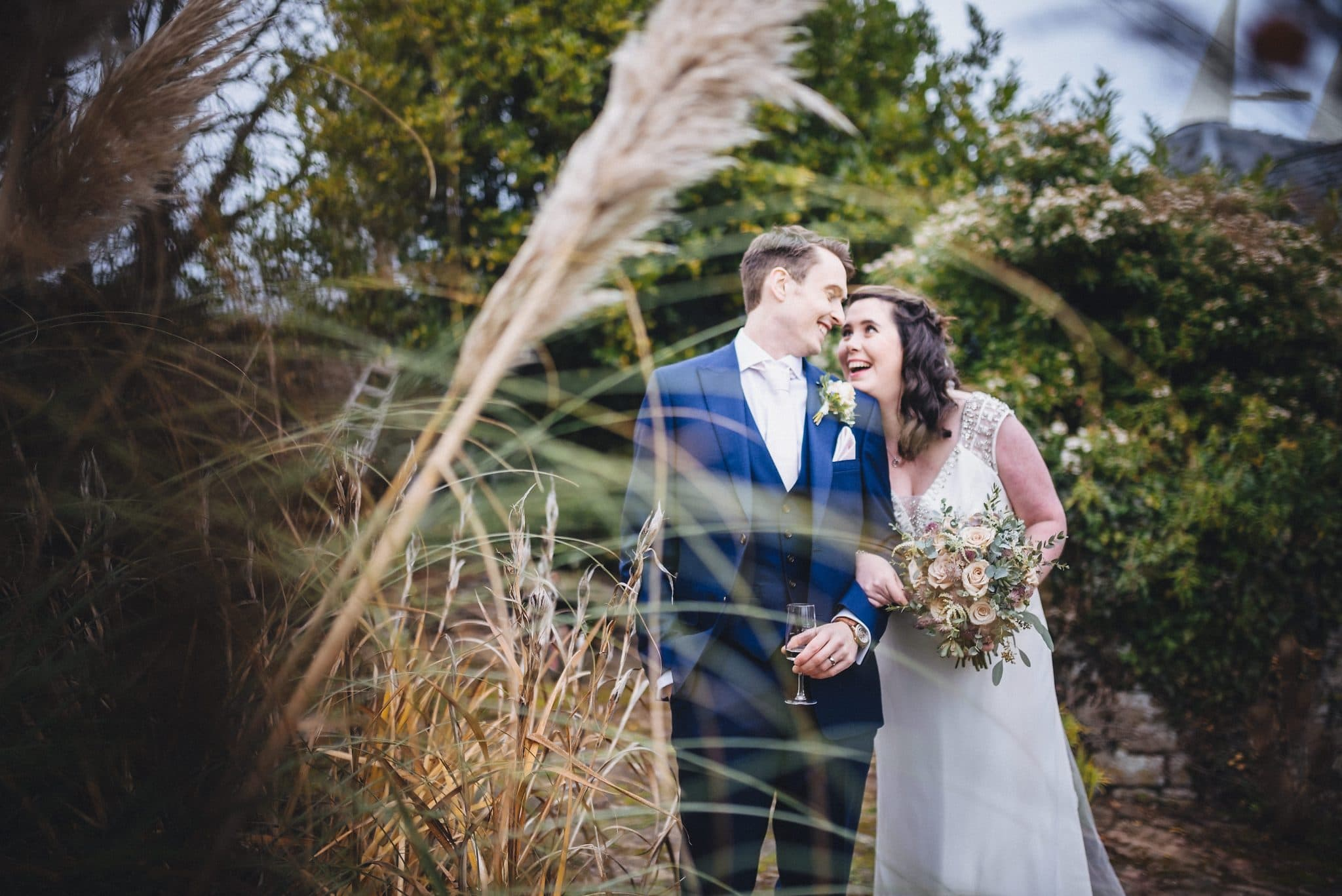 Bride and groom hug and laugh at their Lyde Court winter wedding