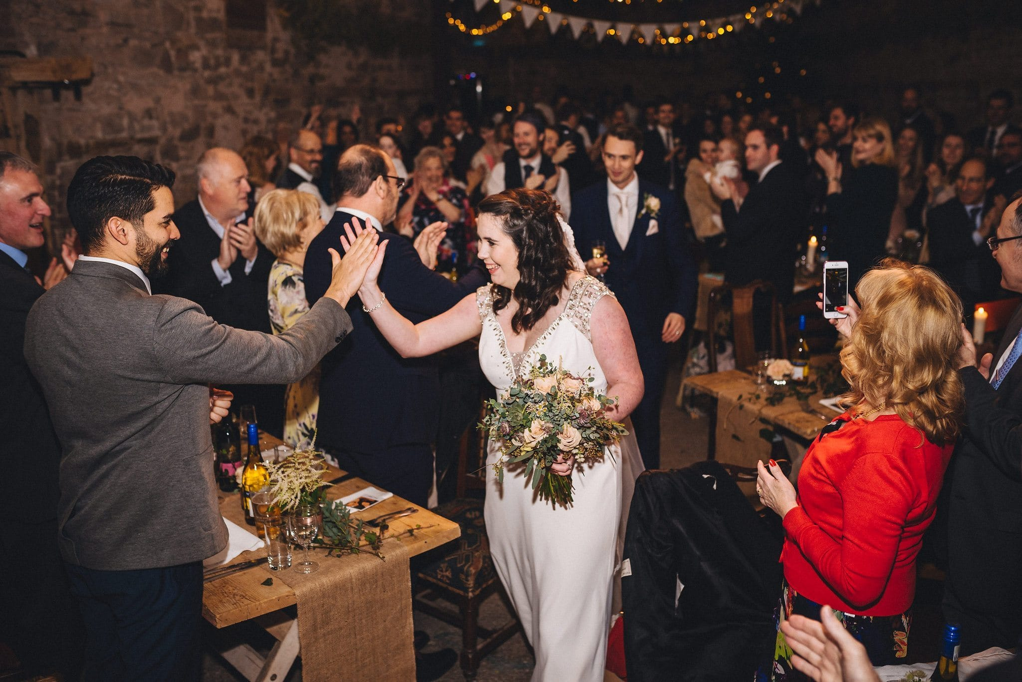 Bride gives guest a high five as she enters the dining room at Lyde Court with her new husband