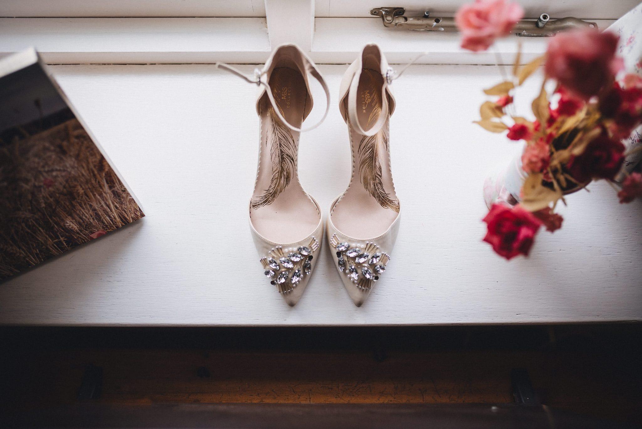 Close up of bride's stilettos on a windowsill
