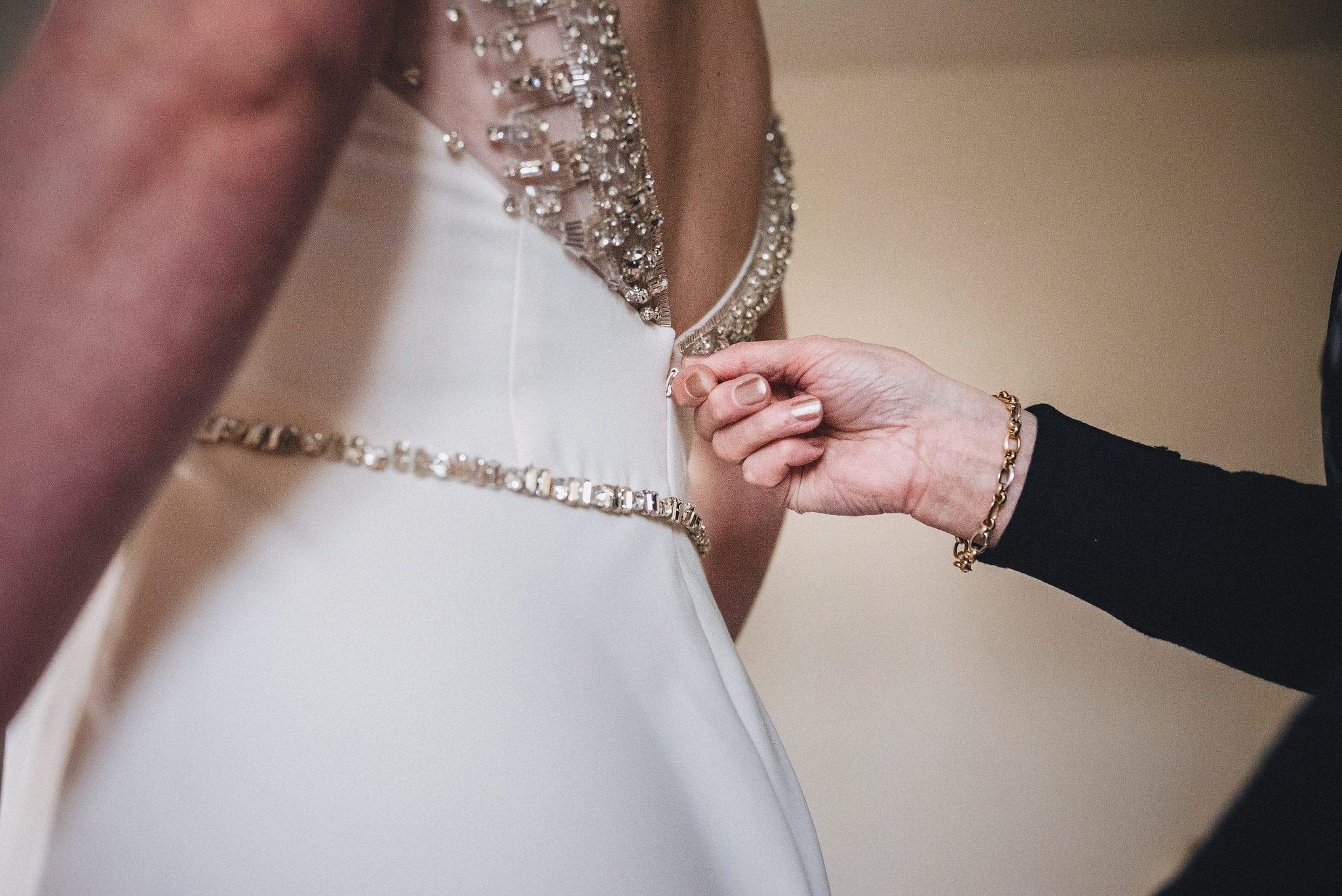 Bride's mother zips her into her wedding dress