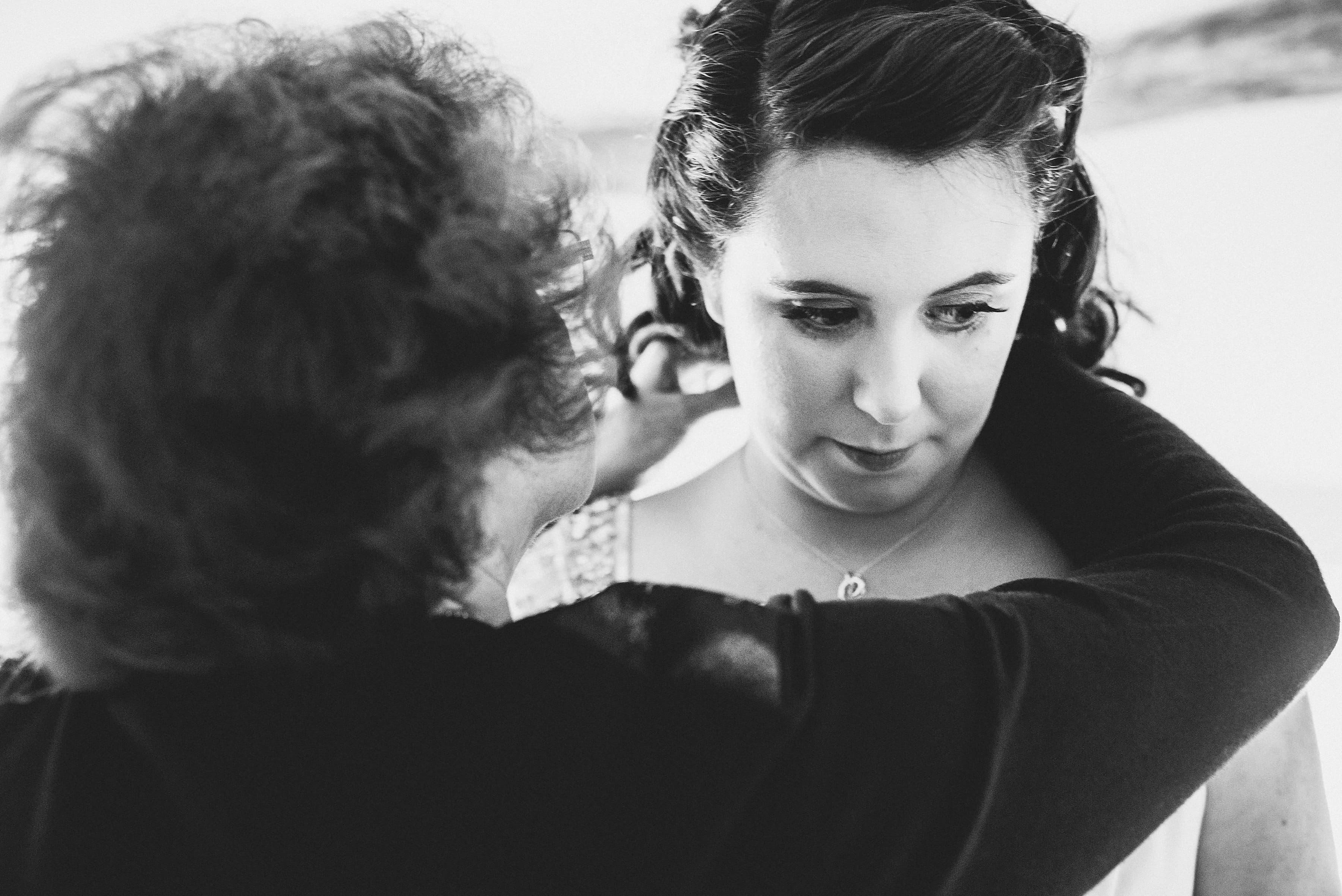 Bride's mum fastens necklace around her daughter's neck
