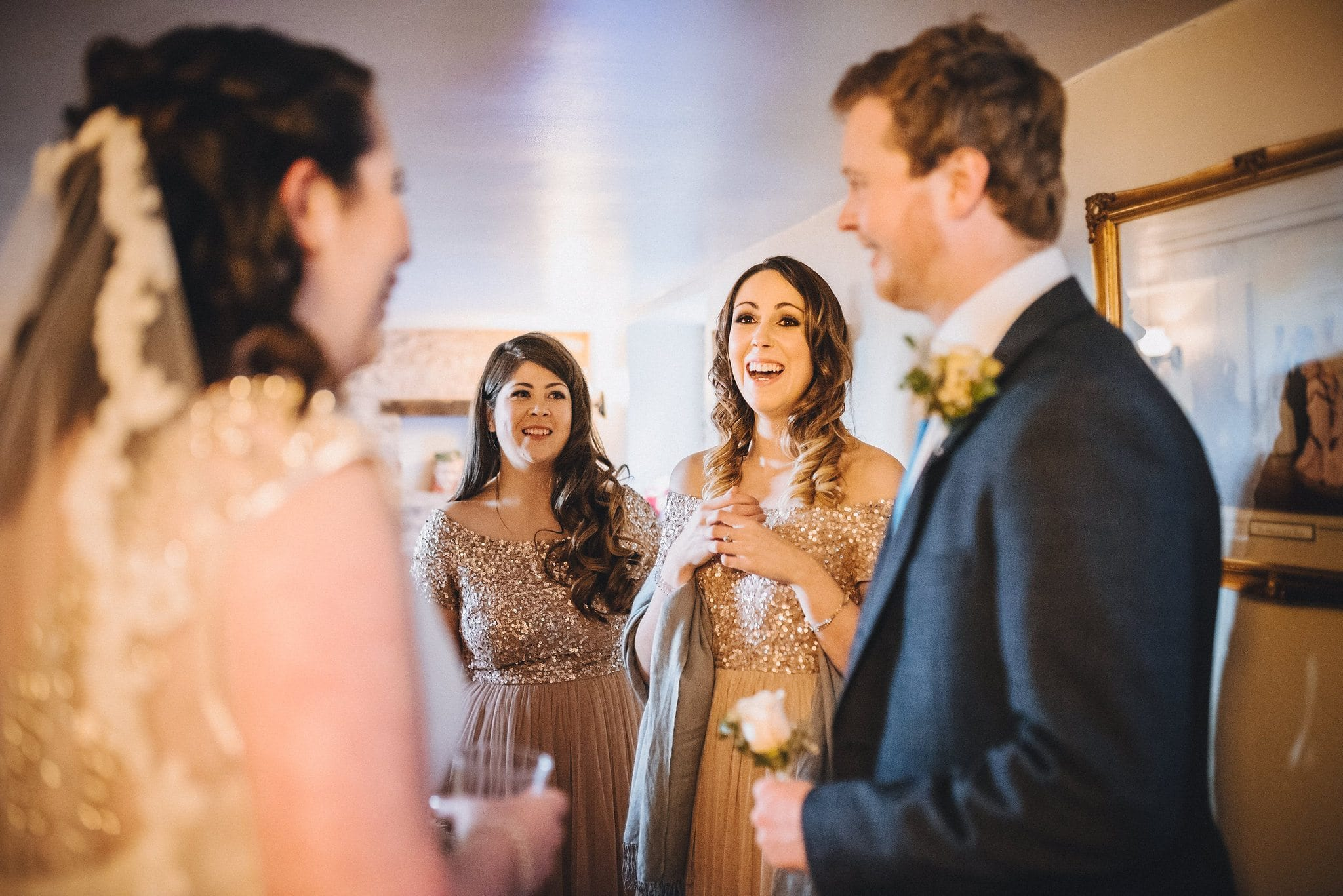 Bridesmaids smile as they see bride in her dress